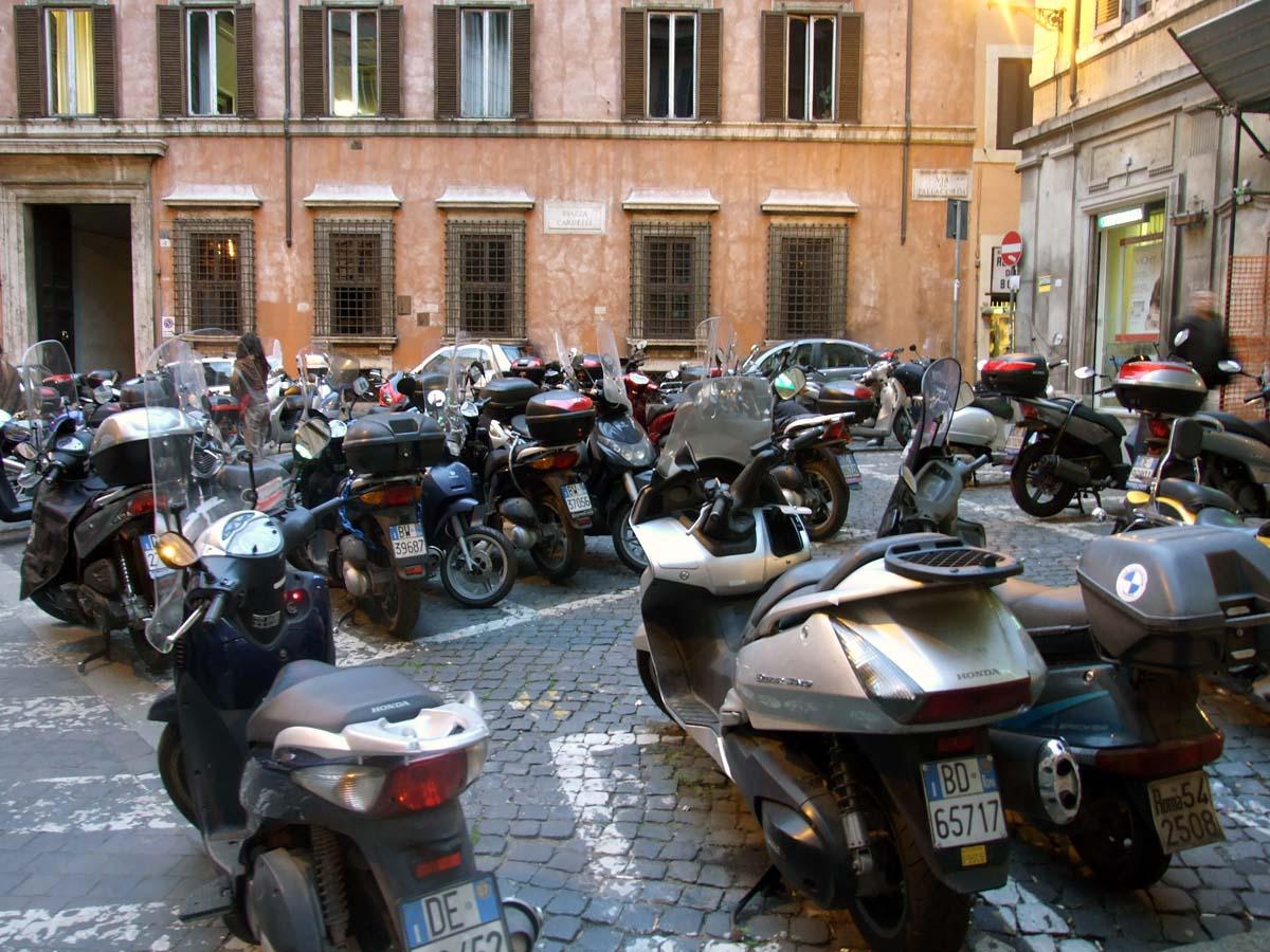 Стоянка скутеров и мотоциклов на одной из узких улиц Рима